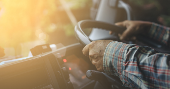 The benefits of defensive driving techniques for truck drivers. Close up image of mans hands on truck steering wheel.